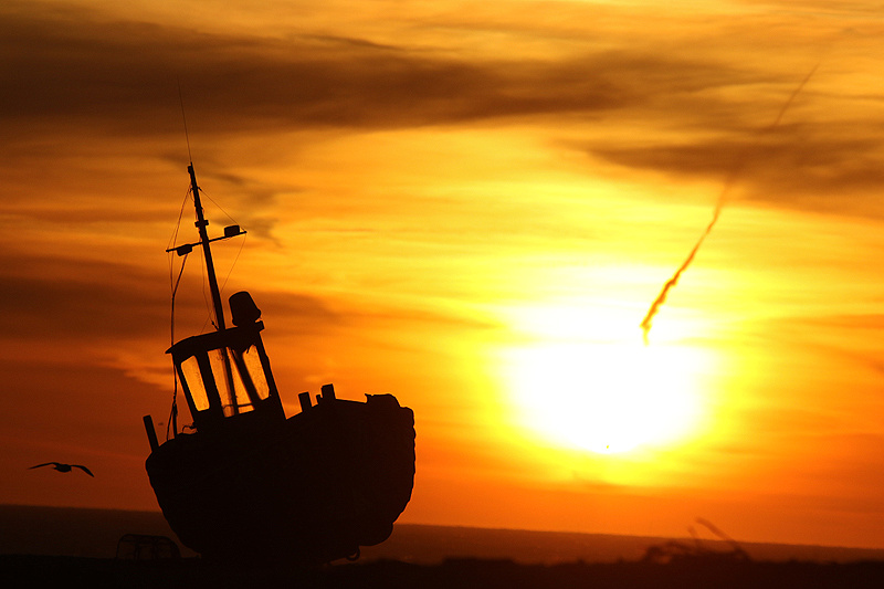 Fishing boat silhouetted against the rising sun
