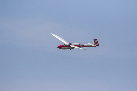 A red and white glider against a blue sky