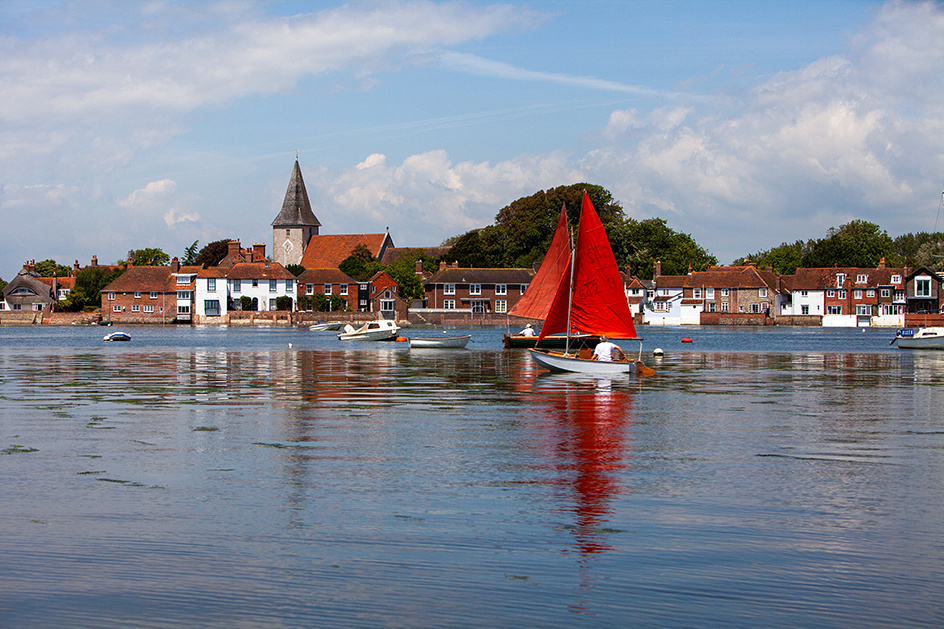 Two small sailing boats with red sails